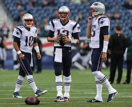 Foxborough, MA - 08/15/14 - New England Patriots quarterback Tom Brady (12) New England Patriots quarterback Ryan Mallett (15), and New England Patriots quarterback Jimmy Garoppolo (10) warm up before the game. The New England Patriots take on the Philadelphia Eagles in a pre-season exhibition game at Gillette Stadium. - (Barry Chin/Globe Staff), Se